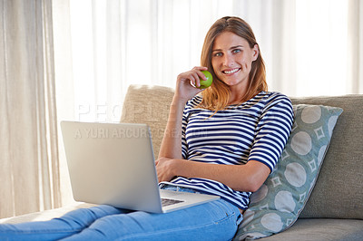 Buy stock photo Shot of a young woman using a laptop on her sofa at home