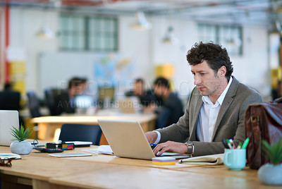 Buy stock photo Shot of a man working on a laptop in a large office