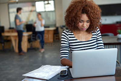 Buy stock photo Shot of a young woman working on a laptop in an office