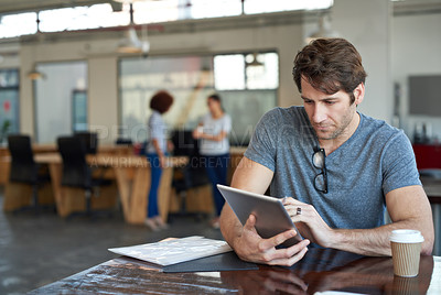 Buy stock photo Shot of a young man working on a digital tablet in an office