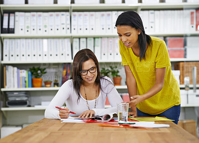 Buy stock photo Shot of a two woman talking together over paperwork in an office
