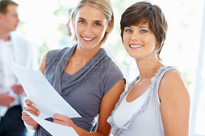 Buy stock photo Two business women holding documents with team in background