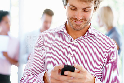 Buy stock photo Young man reading text message with staff in background