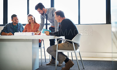 Buy stock photo Shot of four coworkers going over a set of plans together