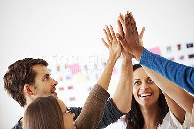 Buy stock photo An excited business team high-fiving one another after completing a project successfully
