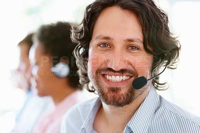 Buy stock photo Customer consultant smiling at you while using headphones with his team blurred in the background
