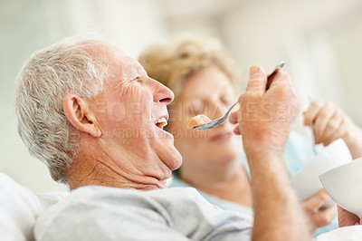 Buy stock photo Shot of a happy senior couple enjoying breakfast in bed together