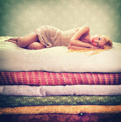 Buy stock photo Portrait of an attractive woman lying on a bed of stacked blankets