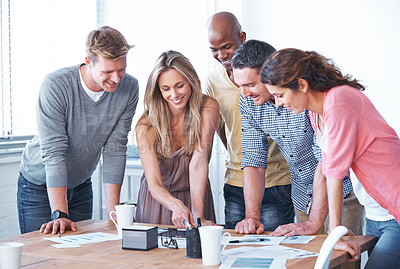 Buy stock photo A diverse group of co-workers looking down at a digital tablet