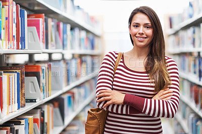 Buy stock photo Shot of a young woman crossing her arms in the library