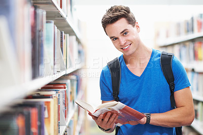 Buy stock photo Shot of an intelligent looking young man holding a book