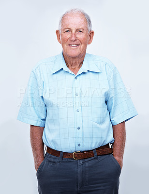 Buy stock photo Studio portrait of a smiling elderly man standing with his hands in his pockets