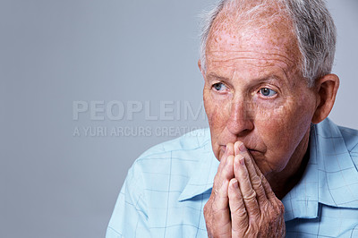 Buy stock photo Studio shot of a sad looking elderly man with his hands on his chin