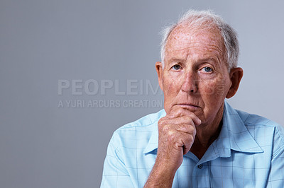 Buy stock photo Studio portrait of a sad-looking elderly man against a gray background