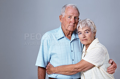 Buy stock photo Studio portrait of an elderly couple embracing each other against a gray background
