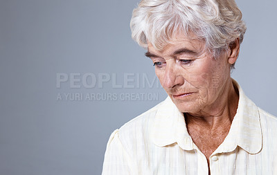 Buy stock photo Studio shot of a grieving senior woman against a gray background