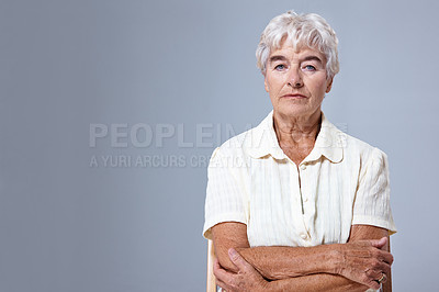 Buy stock photo Studio portrait of a senior woman sitting with her arms crossed against a gray background