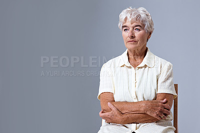 Buy stock photo Studio shot of a senior woman sitting with her arms crossed against a gray background