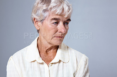 Buy stock photo Studio shot of a depressed looking elderly woman against a gray background