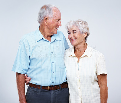 Buy stock photo Studio shot of an happy elderly couple against a gray background