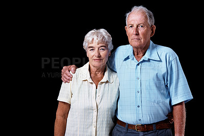 Buy stock photo Cropped studio portrait of an elderly couple isolated on black