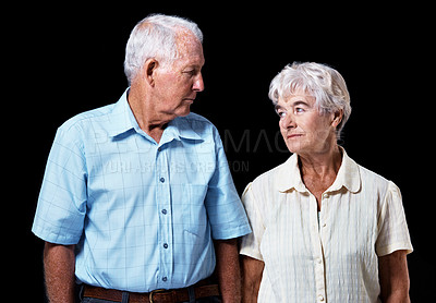 Buy stock photo Studio shot of a senior couple looking at each other isolated on a black background