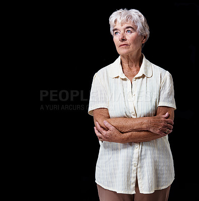 Buy stock photo Studio shot of an elderly woman standing with her arms crossed isolated on black