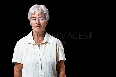 Buy stock photo Studio portrait of an elderly woman standing against a black background