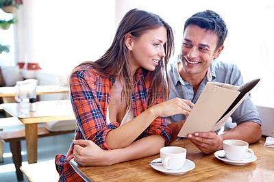 Buy stock photo Shot of a casual couple looking at a menu in a cafe with copyspace