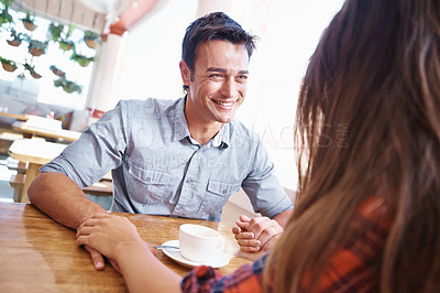Buy stock photo Shot of a smiling couple holding hands across a restuarant table