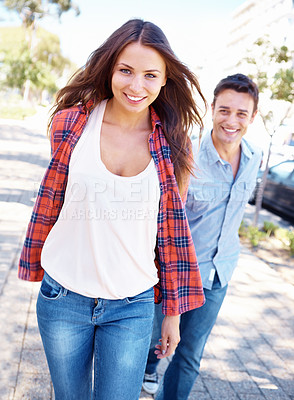 Buy stock photo Shot of a smiling woman walking ahead of her boyfriend while they hold hands