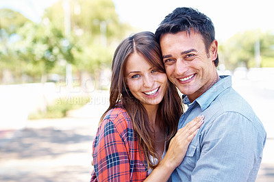 Buy stock photo Portrait of a happy attractive couple smiling at the camera while standing in a park