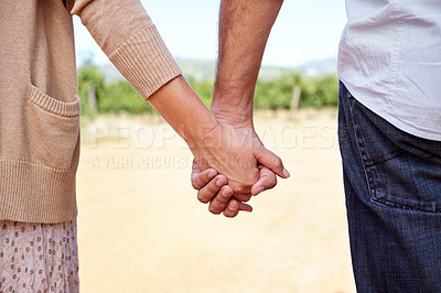Buy stock photo Cropped view of a couple holding hands while looking out over a wine farm