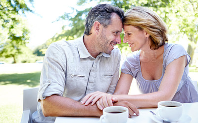 Buy stock photo A happy mature couple having coffee together while out in a garden cafe
