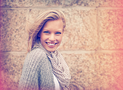 Buy stock photo Cropped portrait of an attractive young woman standing outside against a brick wall
