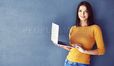 Buy stock photo Portrait of a young woman standing against a gray background using a laptop