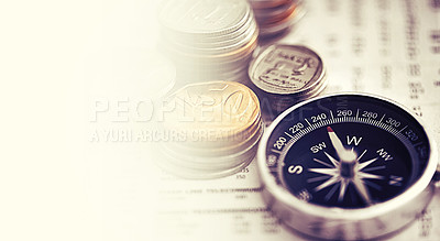 Buy stock photo Studio shot of coins and a compass on the business section of a newspaper