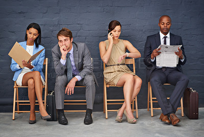 Buy stock photo Full length shot of four people sitting on chairs in line for an interview