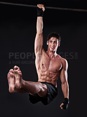 Buy stock photo Studio shot of a young man doing pull-ups from a bar