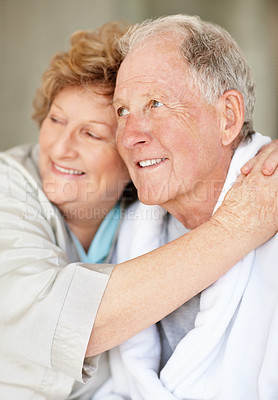 Buy stock photo An affectionate senior woman embracing her husband at home
