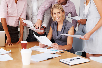Buy stock photo Smiling young woman with team working with documents at meeting