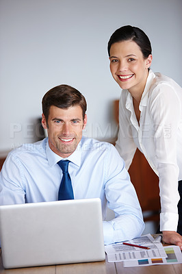 Buy stock photo Portrait of two business colleagues using a laptop in their office