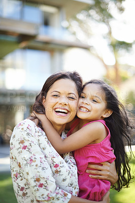 Buy stock photo A cute little girl hugging her mom while they are standing in the garden