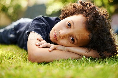 Buy stock photo A cute little boy lying down on the grass in the garden