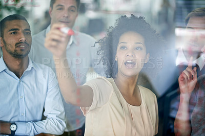 Buy stock photo Shot of a group of creative businesspeople plotting out details on a glass wall