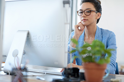 Buy stock photo Professional young woman thinking while looking at the screen of her pc in her office