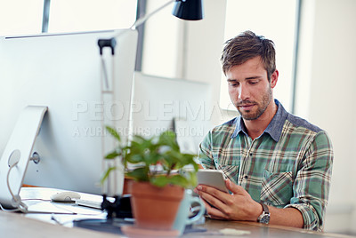 Buy stock photo Shot of a casually-dressed young man using a digital tablet at his desk