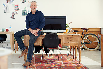 Buy stock photo Portrait of a casually-dressed mature man sitting on his desk in an office