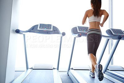 Buy stock photo A beautiful young woman exercising on a treadmill at the gym