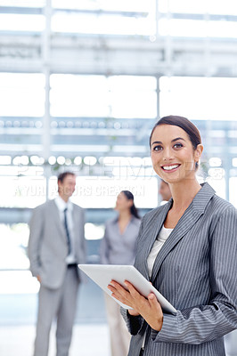 Buy stock photo Smiling young businesswoman using her digital tablet while at work